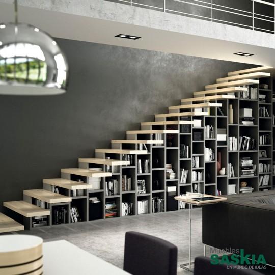 En esta vivienda, se aprovecha el hueco de la escalera para incorporar una amplia librería. Nos ajustamos al milímetro a tus medidas.