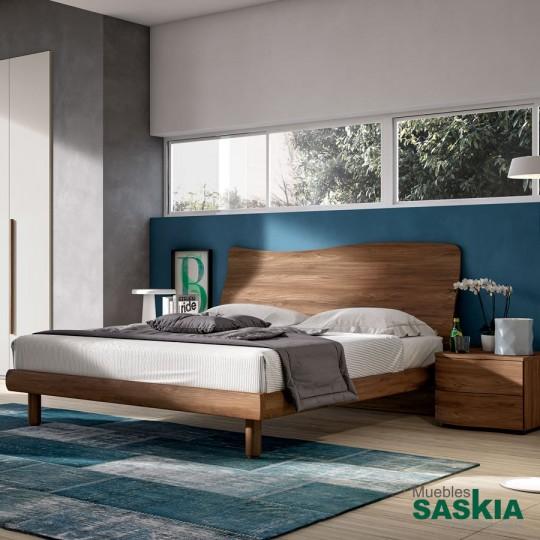Hermosa cama con elegante cabecero de madera.